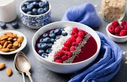 Smoothie bowl with fresh raspberry, blueberry, coconut flakes and chia seeds. Grey stone background. Smoothie bowl with fresh raspberry, blueberry, coconut Royalty Free Stock Image
