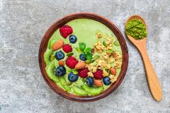Smoothie bowl made of matcha green tea with fresh berries, nuts, seeds with a spoon for healthy vegan breakfast stock images