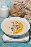 Smoothie bowl with mango, coconut and nuts, vertical royalty free stock photography