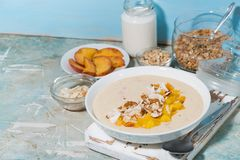smoothie bowl with mango, coconut, oat flakes and nuts stock photos