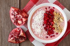 Smoothie bowl with pomegranates, raspberries, coconut, granola over wood Royalty Free Stock Images
