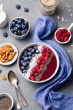 Smoothie bowl raspberry, blueberry, coconut flakes. Smoothie bowl with fresh raspberry, blueberry, coconut flakes and chia seeds. Grey stone background. Top view Stock Photography