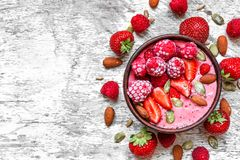 Smoothie bowl with red berries - strawberry and frozen raspberry, nuts and seeds. healthy breakfast. Smoothie bowl with red berries - strawberry and frozen Royalty Free Stock Images