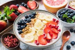 Smoothie bowl with strawberry, banana, blueberry, pomegranate and coconut flakes, closeup view. Concept of healthy lifestyle, healthy eating, vegan, vegetarian Royalty Free Stock Images