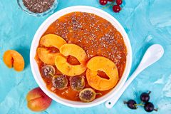 Smoothie bowls. Healthy breakfast bowl on blue background. Apricot smoothie with blackberry and chia seeds. Vegan food. Flat lay. Top view stock photo