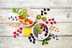 Smoothie breakfast bowls with berries, seeds and nuts on a wood background stock images