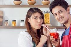 Smoothie de alimentation de fraise de joli homme à son amie photographie stock libre de droits