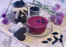 Smoothie de baie en tasse en verre, baies de chèvrefeuille dans la bouteille de vintage et fleurs d'été avec des décorations sur  Images libres de droits