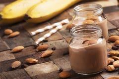 smoothie de Banane-chocolat avec des amandes dans des pots en verre, fond en bois de vintage, foyer sélectif photos libres de droits