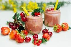 Smoothie de banane et de fraise Deux Smoothies froids de banane de fraise en verres avec des ingrédients sur la table de cuisine  Photos libres de droits