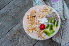 smoothie de Banane-fraise avec le kiwi, le chia, le muesli avec des écrous et la noix de coco dans une cuvette Image libre de droits