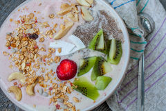 smoothie de Banane-fraise avec le kiwi, le chia, le muesli avec des écrous et la noix de coco dans une cuvette Images libres de droits