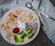 smoothie de Banane-fraise avec le kiwi, le chia, le muesli avec des écrous et la noix de coco dans une cuvette Image stock
