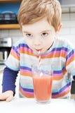 Smoothie de consumición de la fruta del muchacho joven del vidrio Fotos de archivo