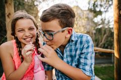 Smoothie de consumición joven feliz del muchacho y de la muchacha junto imagen de archivo
