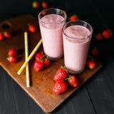 Smoothie de fraise et de banane dans le verre sur le fond noir Images libres de droits