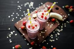 Smoothie de fraise et de banane dans le verre sur le fond noir Photo stock