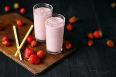 Smoothie de fraise et de banane dans le verre sur le fond noir Image stock