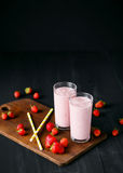 Smoothie de fraise et de banane dans le verre sur le fond noir Photos stock