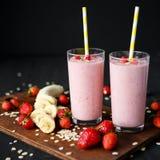 Smoothie de fraise et de banane dans le verre sur le fond noir Photographie stock libre de droits