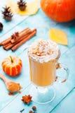 Smoothie de la calabaza, latte de la especia con crema azotada Fondo de madera de la turquesa foto de archivo