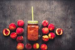 Smoothie de la fruta del melocotón en la botella de cristal y la paja en la tabla de madera Forma de vida sana entonado Imagenes de archivo