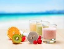 Smoothie de la fruta en la tabla de madera en la playa tropical Imagen de archivo