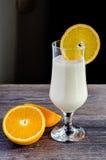 Smoothie de la naranja y del yogur en vidrio en la tabla de madera Foto de archivo libre de regalías