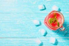 Smoothie de la sandía en tarro con las rebanadas frescas de la sandía en la opinión superior del fondo azul Imagenes de archivo