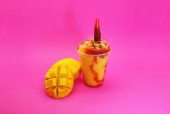 Smoothie de mango con Chamoy. Licuado de mango con picante , Sobre fondo amarillo , Servido en vaso plástico y popote Stock Image