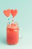 Smoothie de pastèque dans le pot de maçon avec des tranches de pastèque de coeur sur des pailles Photo stock
