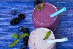 Smoothie del arándano y de la zarzamora en fondo de madera azul Batido de leche con las bayas frescas smoothie sano de la fruta c foto de archivo libre de regalías