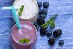 Smoothie del arándano y de la zarzamora en fondo de madera azul Batido de leche con las bayas frescas smoothie sano de la fruta c imagenes de archivo