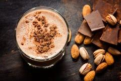 smoothie del chocolate en un fondo oscuro con el chocolate y las nueces Foto de archivo