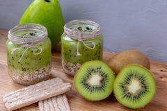 Smoothie del kiwi con el cereal en una tabla de madera foto de archivo