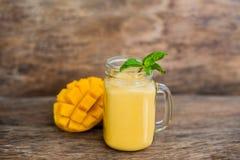 Smoothie del mango en un tarro y un mango de cristal de albañil en el viejo fondo de madera Sacudida del mango Foto de archivo libre de regalías