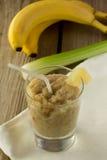 Smoothie del plátano y del apio con las bayas en la tabla de madera Fotografía de archivo libre de regalías
