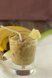 Smoothie del plátano y del apio con las bayas en vertical de madera de la tabla Foto de archivo