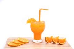 Smoothie del zumo de naranja y rebanadas de naranja en el fondo blanco Imagen de archivo libre de regalías