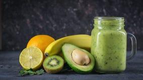 Smoothie der Avocado, der Banane, der Kiwi und der Zitrone auf einem Holztisch gegen eine schwarze Wand Vegetarisches Lebensmitte Stockbild
