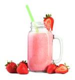 Smoothie doux de fraise en pot de maçon et beaucoup de fraises rouges savoureuses et lumineuses autour, sur un fond blanc Photo stock