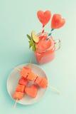 Smoothie doux de pastèque dans le pot de maçon avec la menthe, pailles, tranches de pastèque de coeur sur le bleu Image libre de droits
