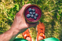 Smoothie drink a sport man in a nature. Glasses of smoothie with berry and mint. Berry, leaf and lime, raspberriesFruit Healt. Hy food stock photo