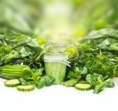 Smoothie en verre au-dessus de fond vert de légumes sur la table blanche Photos stock