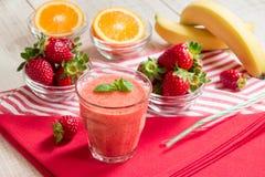 Smoothie et ingrédients oranges de banane de fraise Photographie stock libre de droits