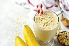 Smoothie för bananjordnötsmör med havre och kanel i ett exponeringsglas arkivbild