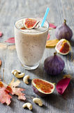 Smoothie with figs and cahew. Healthy beverage with fruits wooden background Royalty Free Stock Photo