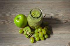 Smoothie frais de kiwi avec la pomme et les raisins dans une bouteille Photographie stock libre de droits