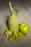 Smoothie frais de kiwi avec la pomme et les raisins dans une bouteille Image stock