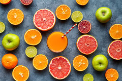 Smoothie or fresh juice vitamin drink in sliced citrus fruits background flat lay royalty free stock images